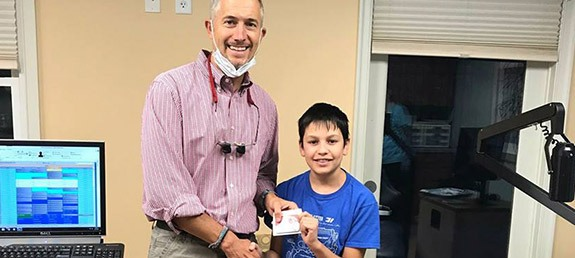 Dr. DeMaio smiling with young patient