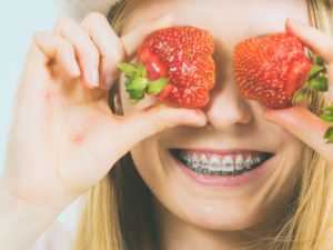 Woman at orthodontist holding strawberries